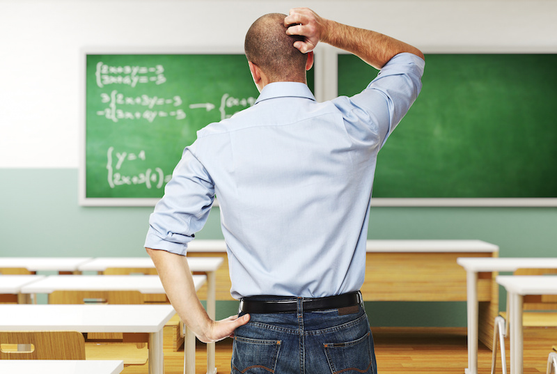 standing man thinking infront of blackboard